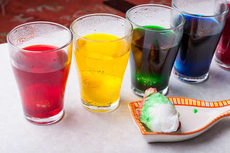 Coloring eggs before the church holiday of Easter at home - a solution with food coloring of different colors diluted in glasses and design with paper napkins. 写真素材