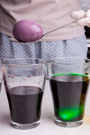 Close-up of a dyed boiled egg extracted from a purple food coloring solution using a spoon next to a glass of green paint on a white kitchen table.