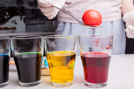 Preparing for Easter coloring eggs in home kitchen female hands in rubber gloves with help spoon take boiled egg from glass with red dye next other glasses multi-colored solutions with submerged eggs 写真素材