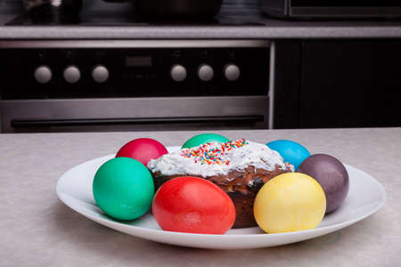 Easter holiday with colorful eggs and Easter cake on a plate while cooking. Homemade cakes in the kitchen.