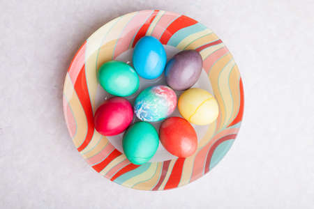 Easter holiday with colorful eggs on a plate while cooking. Homemade baking.