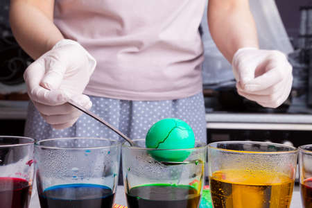 Preparing for Easter - coloring eggs in home kitchen female hands in rubber gloves use spoon take boiled egg out of glass with diluted green dye next other glasses different colors with submerged eggs 写真素材