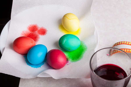 Dyed boiled eggs in red, yellow, green, blue and orange dry on a white paper napkin on a plate - preparing for Easter at home in the kitchen.
