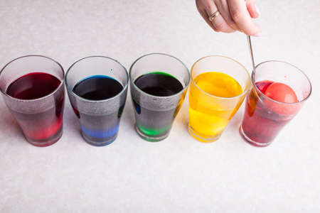 Preparing for the Christian holiday of Easter - dyeing boiled eggs in the home kitchen in different colors by immersing them in glasses with diluted food coloring using a spoon.