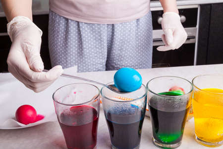 Preparing for Easter - dyeing eggs in home kitchen female hands in rubber gloves use a spoon to take a boiled egg out of a glass with blue dye next to other multi-colored solutions with submerged eggs 写真素材