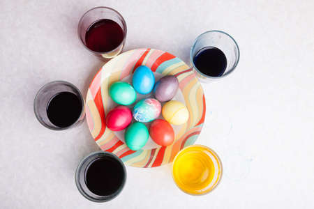 Easter holiday with colorful eggs on a plate while cooking with glasses of shell paint. Homemade baking.