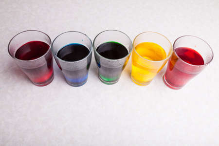 Transparent glasses on a white kitchen table in a line filled with a multi-colored liquid of red blue green yellow, diluted food coloring prepared for coloring eggs before Easter.