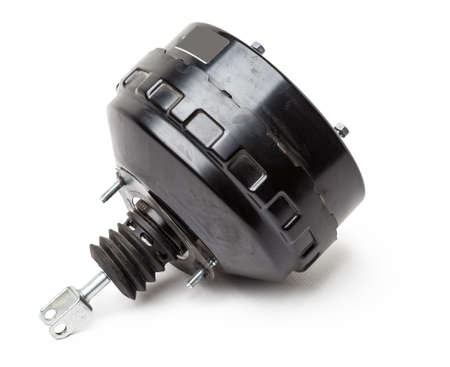 Black metal vacuum brake booster for repair and replacement on a car in a workshop on a white isolated background. Spare parts catalog for cars. 写真素材