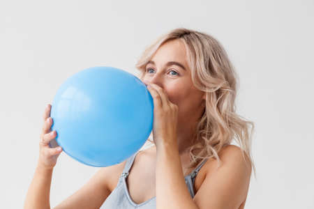 A beautiful young pregnant woman with a big belly in blue jeans holds a balloon that means that a boy will be born. 写真素材