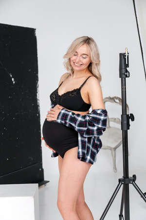 Beautiful pregnant blonde woman in underwear at a photo session in the studio with equipment for high-quality and beautiful pictures. 写真素材