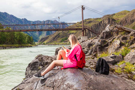 a young beautiful blonde woman in a pink suit with shorts sits on a large stone near the river in the Altai mountains and looks into the phone against the background of an old iron bridge. Stock fotó