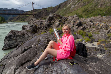 a young beautiful blonde woman in a pink suit with shorts sits on a large stone near the river in the Altai mountains and holds an iron  with tea in her hands while relaxing in vacation