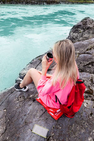 a young beautiful blonde girl in a pink suit with shorts sits on a large stone near the river in the altai mountains and drinks hot tea from an iron mug while relaxing Stock fotó - 166583321