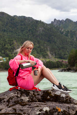 a young beautiful blonde girl in a pink suit with shorts sits on a large stone near the river in the Altai mountains and pours hot tea from an iron thermos into a mug while relaxing