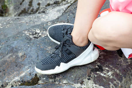 close-up on the legs of a woman in black sneakers with white soles for sports and walks in the fresh air in the mountains on the rocks.