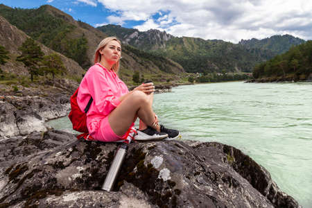 a young beautiful blonde girl in a pink suit with shorts sits on a large stone near the river in the Altai mountains and holds hot tea in her hands in an iron mug while relaxing Stock fotó