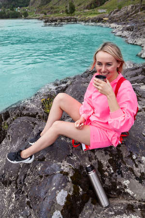a young beautiful blonde girl in a pink suit with shorts sits on a large stone near the river in the altai mountains and drinks hot tea from an iron mug while relaxing Stock fotó - 166583338