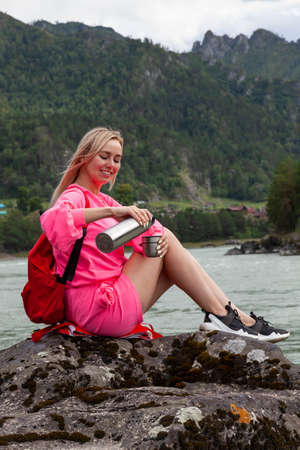 a young beautiful blonde girl in a pink suit with shorts sits on a large stone near the river in the Altai mountains and pours hot tea from an iron  into a mug while relaxing