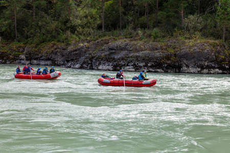 Novosibirsk, Russia - 08.14.2020: A team of people rafting in orange life jackets on rubber boat of blue and yellow colors along a mountain river against the background of a rocky shore with a forest