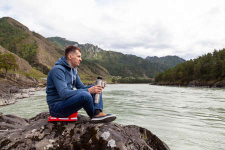 A brunette man of Caucasian appearance sits on a stone near the Katun river in the Altai mountains and drinks tea pouring into a mug from a  on a cool autumn day.