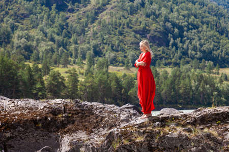Blonde woman in red dress stands on the rock stones on banks of Katun river against background of mountains on summer. WAiting for wonder. Assol. suicidal mood Stock fotó