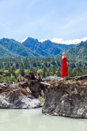 Blonde woman in red dress stands on the rock stones on banks of Katun river spread her arms to the sides before jumping against background of mountains on summer. Assol. suicidal mood