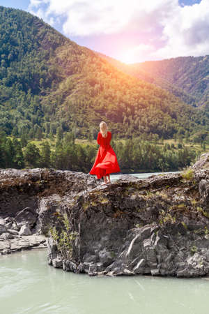 view from the back of Blonde woman in red dress with arms hugging herself, stands on the rock stones on banks of Katun river against background of mountains on summer. WAiting for wonder. Assol. Stock fotó