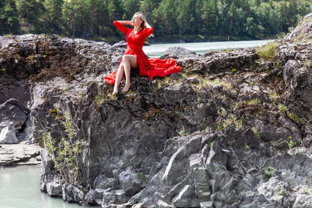 Blonde woman in red dress straightens hair with his hands, sits stretching her long legs on the rock stones on banks of Katun river against background of mountains on summer. Freedom and vacation.