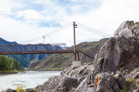 Picturesque landscape in the Altai mountains near the rocks on the river bank with an old iron rusty bridge.