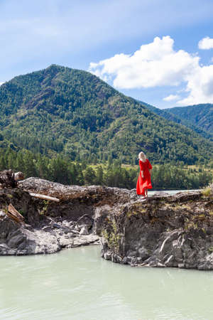 view from the back of Blonde woman in red dress stands on the rock stones on banks of Katun river against background of mountains on summer. WAiting for wonder. Assol. suicidal mood Stock fotó