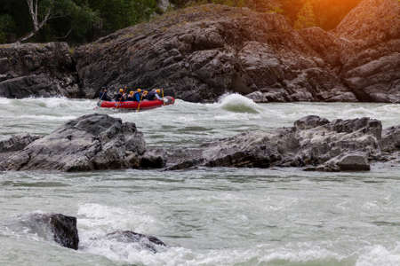 A team of people rafting in orange life jackets on an rubber boat of blue and yellow colors along a mountain river against the background of a rocky shore with a forest. Stock fotó - 166571551