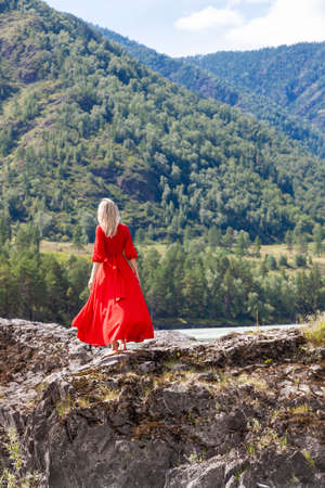 view from the back of Blonde woman in red dress fluttering in the wind stands on the rock stones on banks of Katun river against background of mountains on summer. WAiting for wonder. Assol.