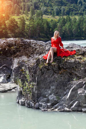 Blonde woman in red dress sits stretching her long legs on the rock stones on banks of Katun river against background of mountains on summer. Freedom and vacation.