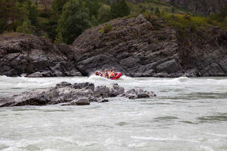 A team of people rafting in orange life jackets on an rubber boat of blue and yellow colors along a mountain river against the background of a rocky shore with a forest. Stock fotó