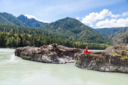 Blonde woman in red vintage dress with arms folded on her chest, hugging herself, sits stretching her long legs on the rock stones on banks of Katun river against background of mountains on summer. Stock fotó