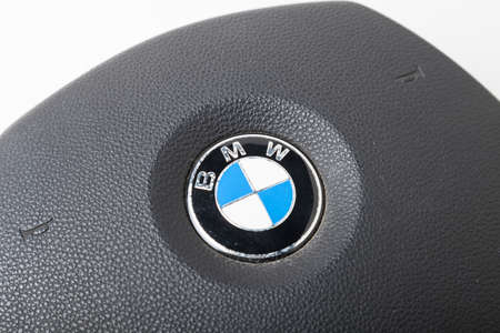 Novosibirsk, Russia - 09.03.2020: Close up view emblem from a BMW car driver airbag in the steering wheel on a white isolated background. Auto service industry. Editorial