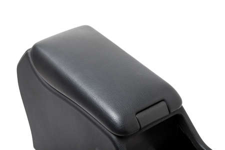 Plastic element of car interior is covered in black leather - armrest or a glove compartment - spare part with air conditioning holes on a white background. Catalog for site.