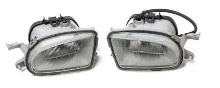 Spare part for sale at auto-parsing or car body repair in service on a white isolated background in a photo studio - a pair of fog lamps, after an accident and damage.