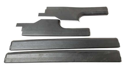 A four of black plastic decorative door sills in an automobile parsing for sale or repair in a workshop on a white isolated background in a photo studio. Foto de archivo