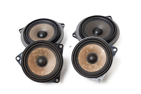 Four speakers of an acoustic system - an audio for playing music in a car interior on a white isolated background in a photo studio. Spare parts for auto repair in a workshop or for sale for tuning