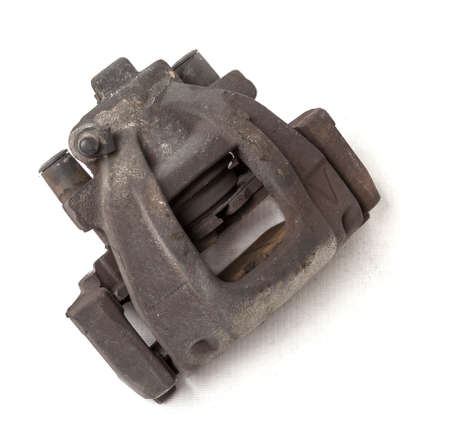 Old metal brake caliper on a white background in a photo studio for replacement during the repair of the chassis or for a catalog of spare parts for sale on auto parsing. Foto de archivo