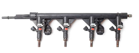 Close-up on a car fuel rail with injectors for supplying gasoline to a four cylinder engine on a white isolated background. Spare parts catalog.