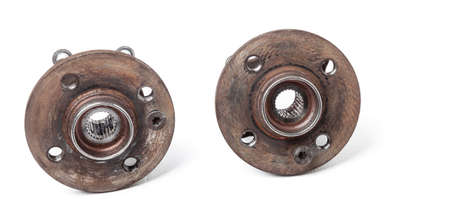 Wheel hub with bearing from old metal close-up on white isolated background in a photo studio. Seasonal repair of the suspension and braking system in the workshop or spare parts for sale.