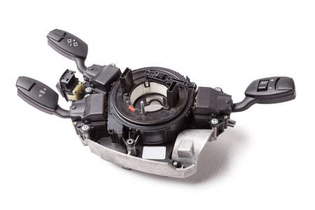 Steering wheel understeering switches for windshield wipers and turn signals with steering angle sensor disassembled on a white isolated background, spare part for car repair or for sale at junk yard.