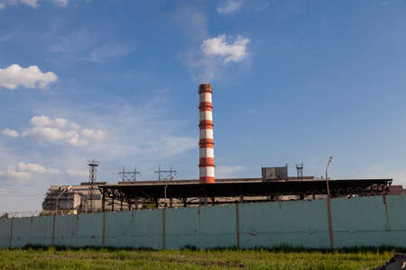 Smoking industrial stack in a thermal power plant emit polluted air into the atmosphere in the blue sky