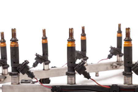 Close-up on a car fuel rail with injectors for supplying gasoline to eight cylinder engine on a white isolated background. Spare parts catalog.