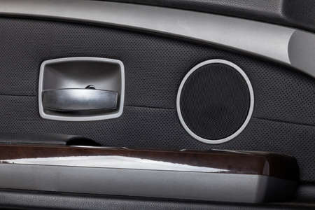 Luxury car door interior with leather upholstery and speaker grille. Comfort car driving.