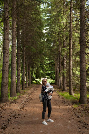 Beautiful mother with a child in the autumn forest, a mother with her son on a walk, a woman blonde with long hair Stock fotó