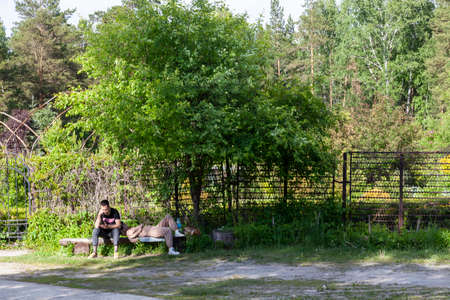 Novosibirsk, Russia - 06.12.21: Young romantic couple talking to each other on a bench at sunset. Happy couple relaxing on a bench in the forest while walking in the garden