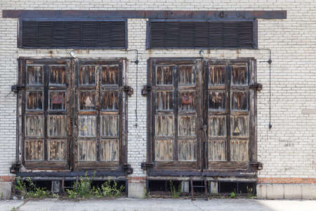 Large old wooden doors in a brick building for servicing electrical communications.